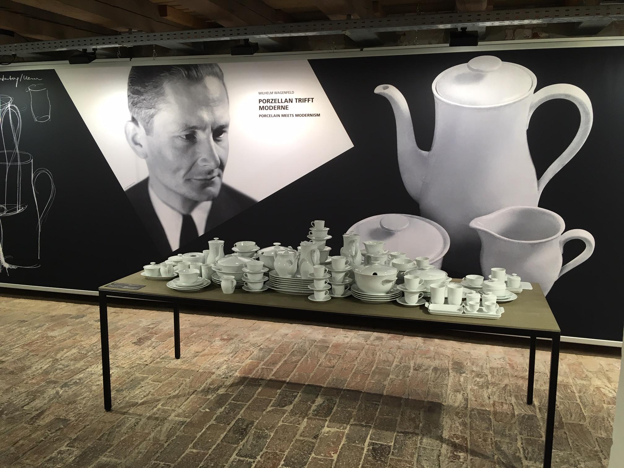 Im Vordergrund ein Tisch, auf dem steht ganz viel weißes Porzellan von Wilhelm Wagenfeld, im Hintergrund ein Bild von Herrn Wagenfeld und eine Kaffeekanne aus Porzellan