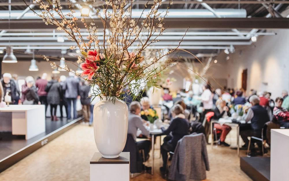 Porzellanvase mit großesm Blumenstrauß im Vordergrund, Personen an Tischen sitzend im Hintergrund