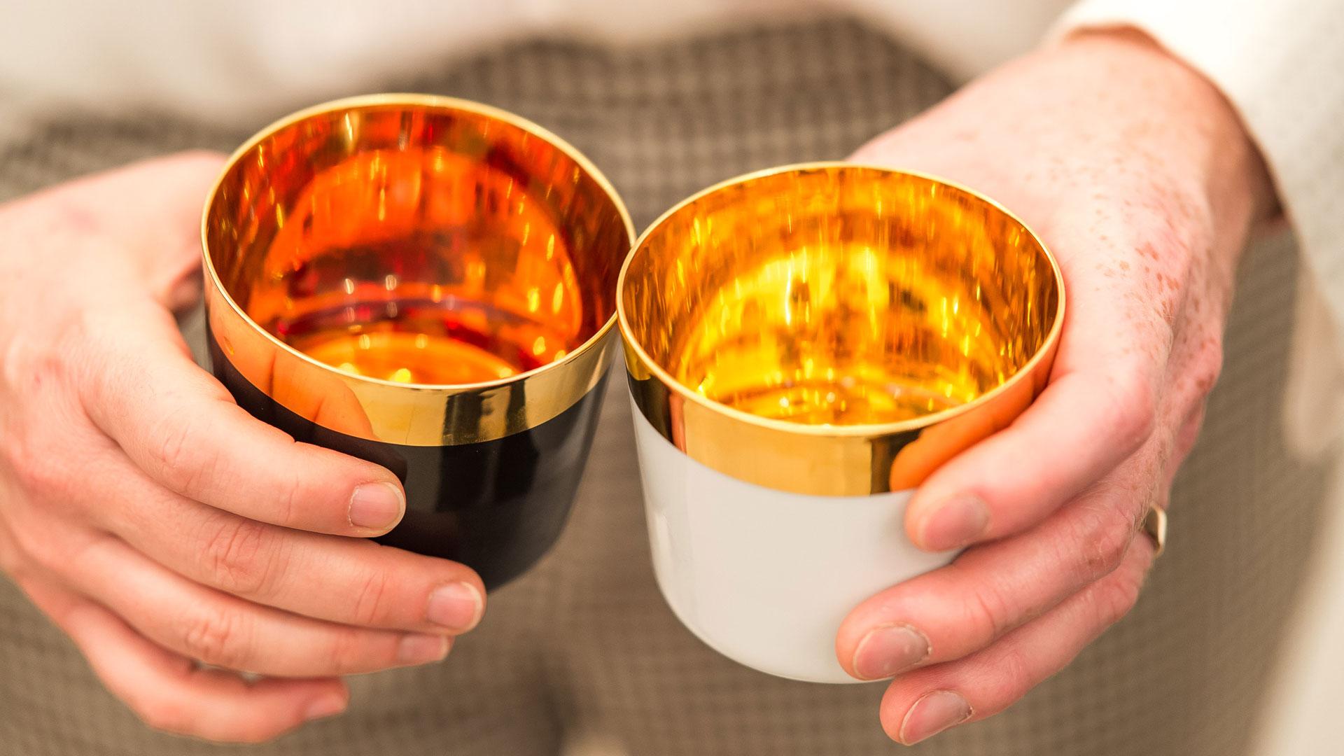 Zwei Hände mit je einem Champagnerbecher in schwarz und einem in weiß, gefüllt mit Wasser, Becher sind von innen vergoldet