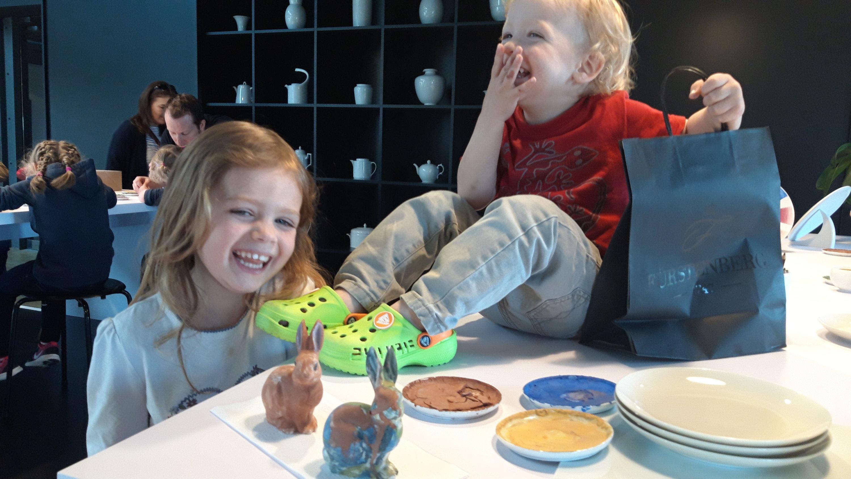 Zwei Kinder in der Besucherwerkstatt beim Bemalen von Porzellanhasen