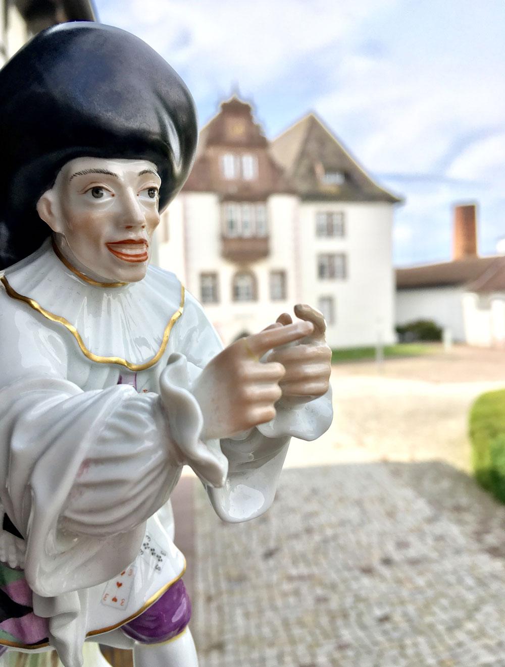 Porzellanfigur, im Hintergrund das Schloss FÜRSTENBERG