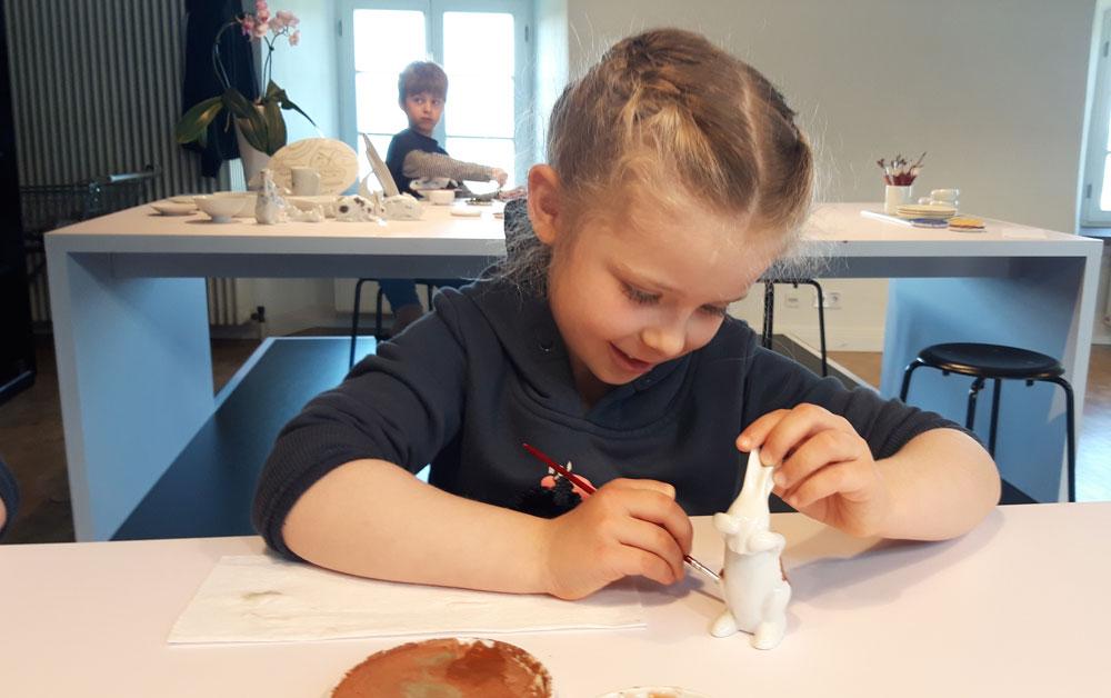 Junges Mädchen beim Bemalen eines Porzellanhasen in der Besucherwerkstatt.