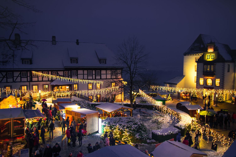Blick auf den Schlosshof beim Weihnachtsmarkt, schneebedeckte Hütten, Lichterketten
