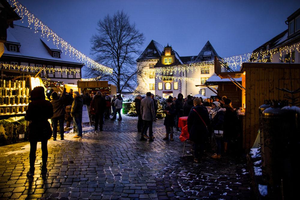 Blick auf den erleuchteten Schlosshof mit Weihnachtsmarktbuden