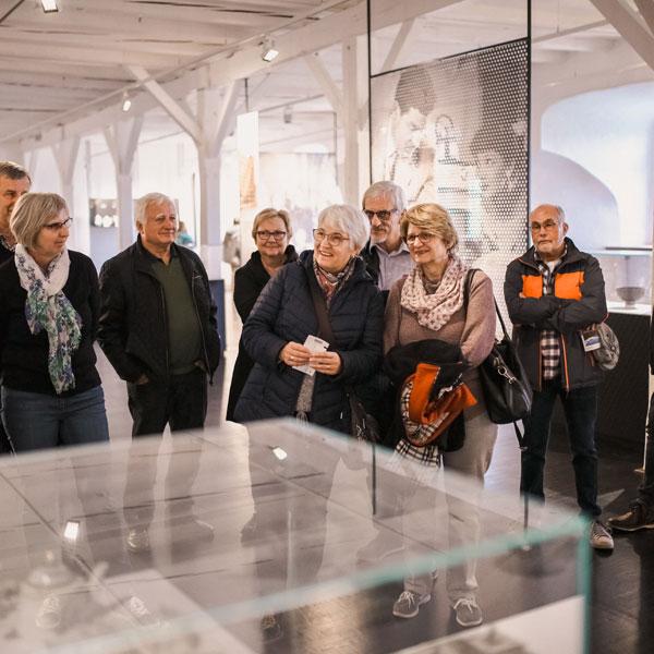 Gruppe von Besuchern vor einer Vitrine im Museum