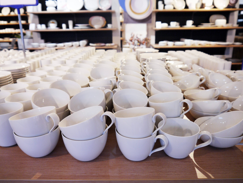 Blick auf einen Tisch, der mit weißen Porzellantassen gefüllt ist