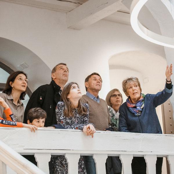 Familie bei einer Führung im Treppenhaus im Museum
